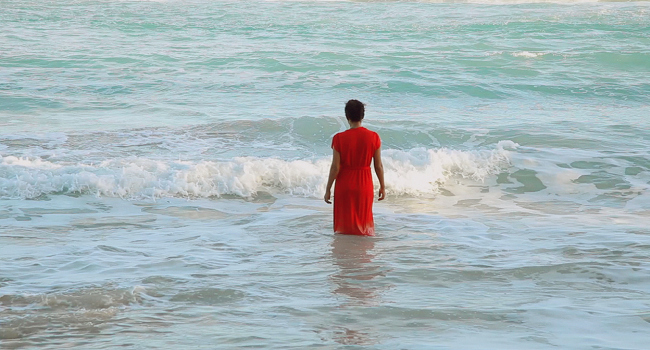haitian woman in red dress standing in ocean waves