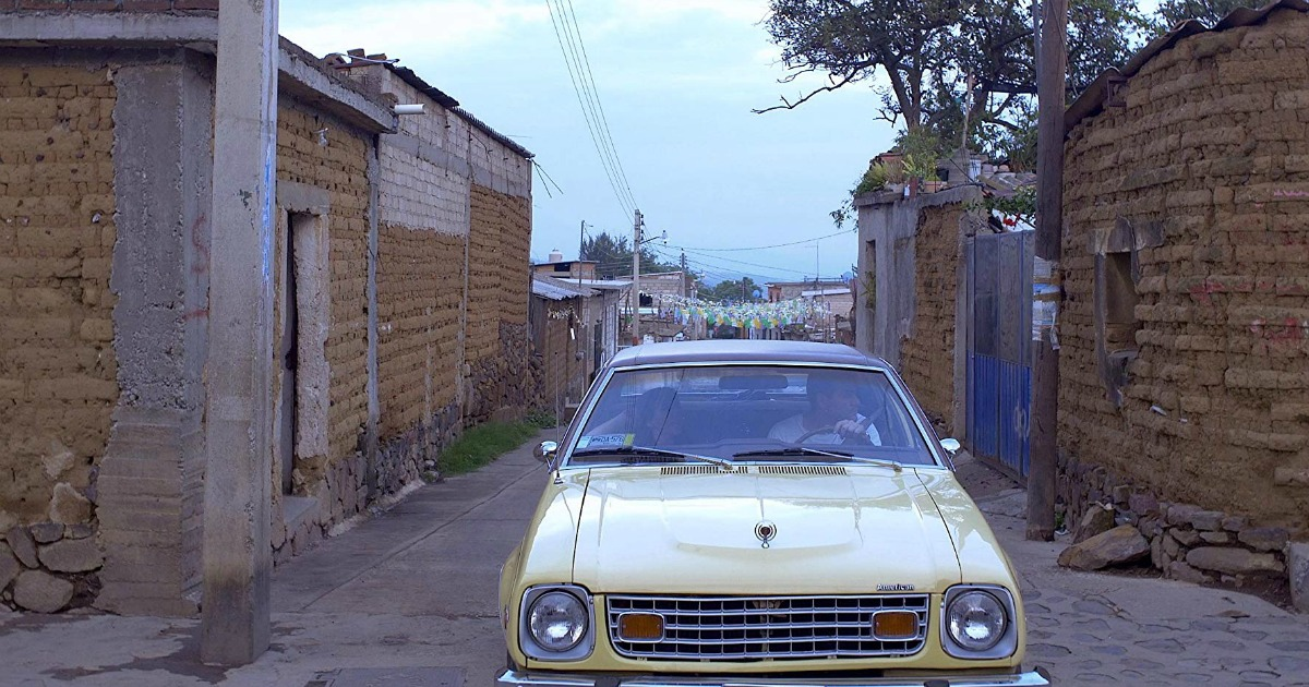 couple in yellow car on narrow road with old buildings on both sides