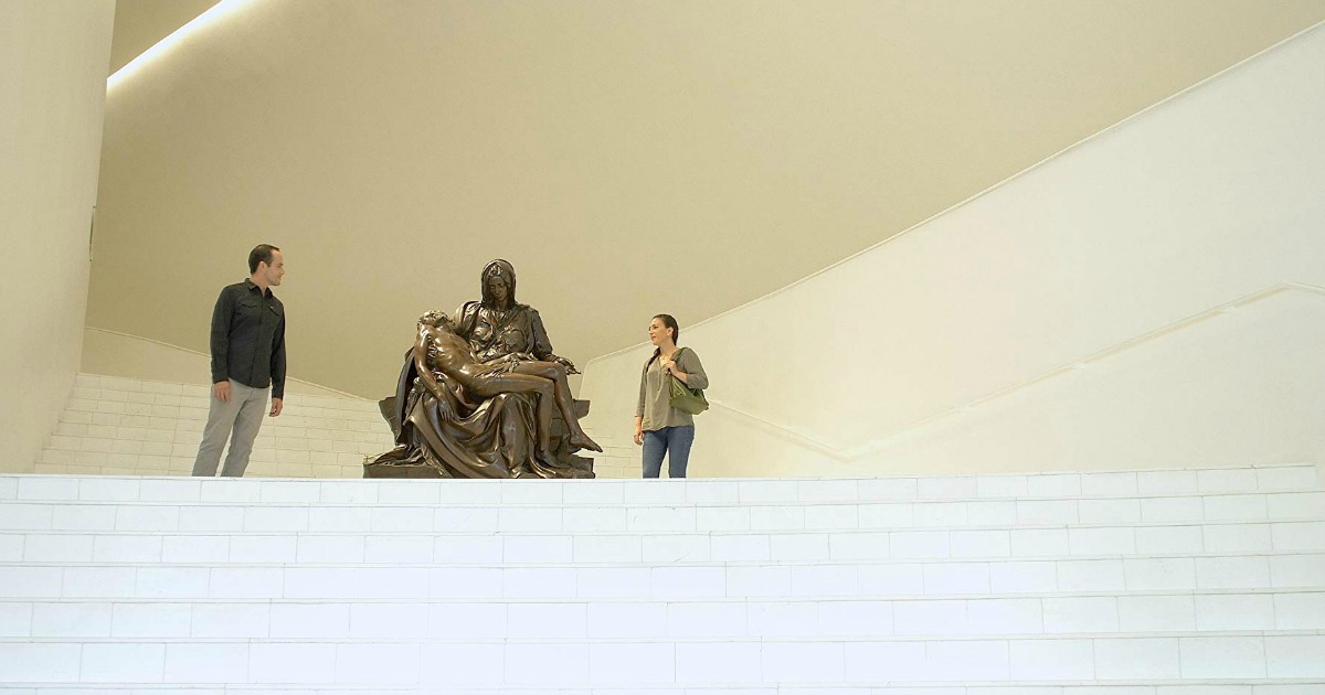 man and woman viewing statue