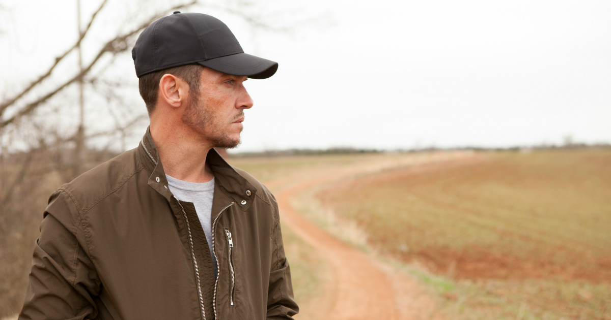 man in brown jacket gazing out upon field