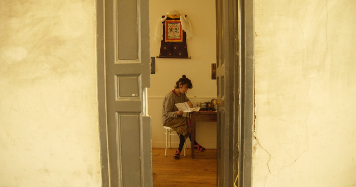 looking through a doorway at a woman reading a book
