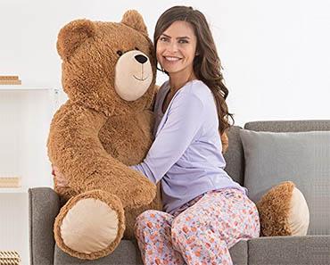 woman cuddling giant teddy bear