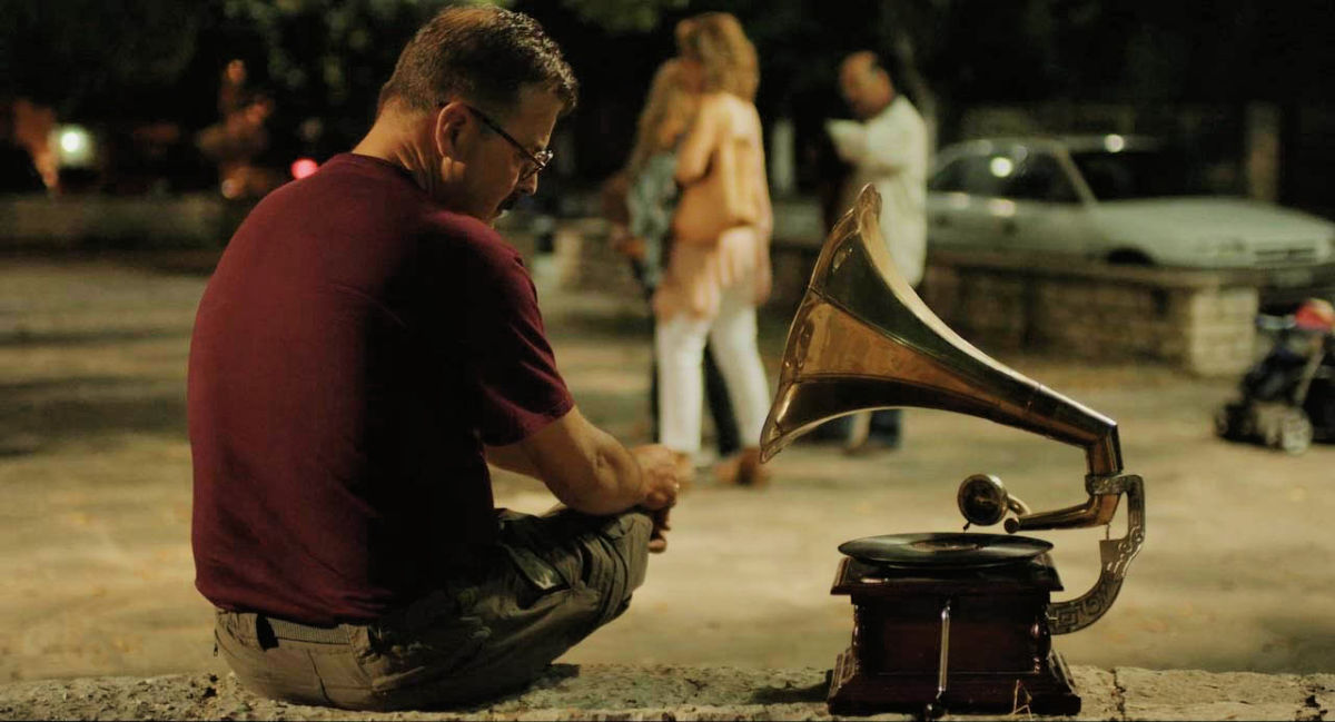 man listening to old victrola
