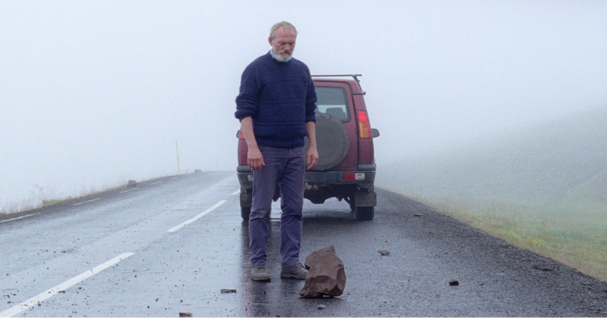 man looking at rock in the road