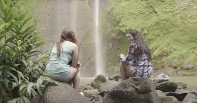 women talking in front of waterfall