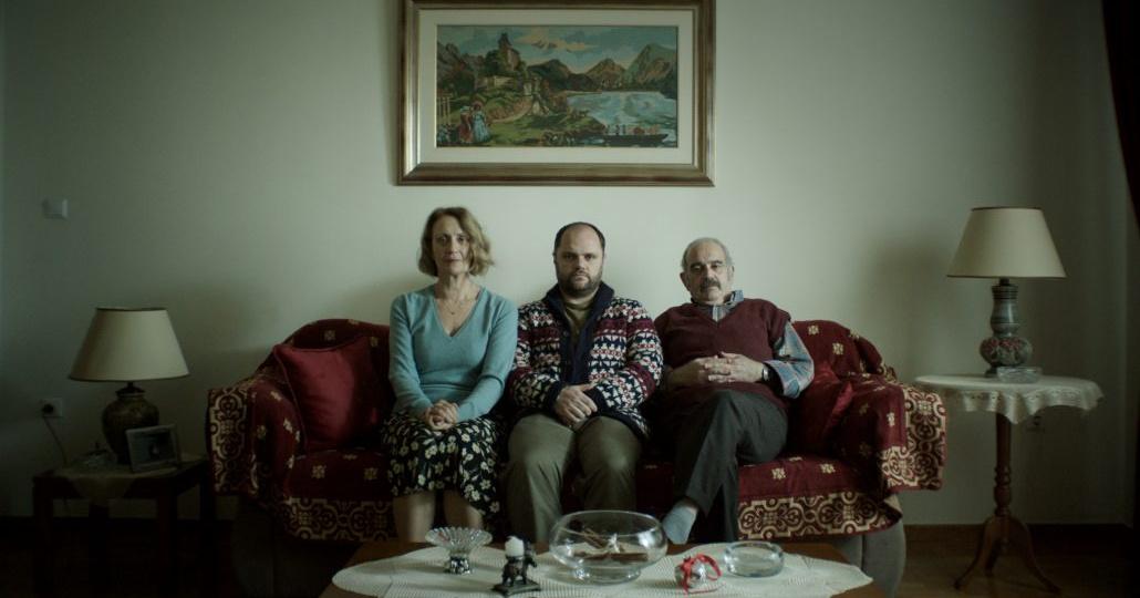three adults sitting on sofa