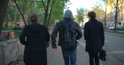 three russian comrades walking on sidewalk