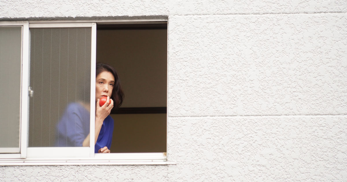 woman looking out window eating apple