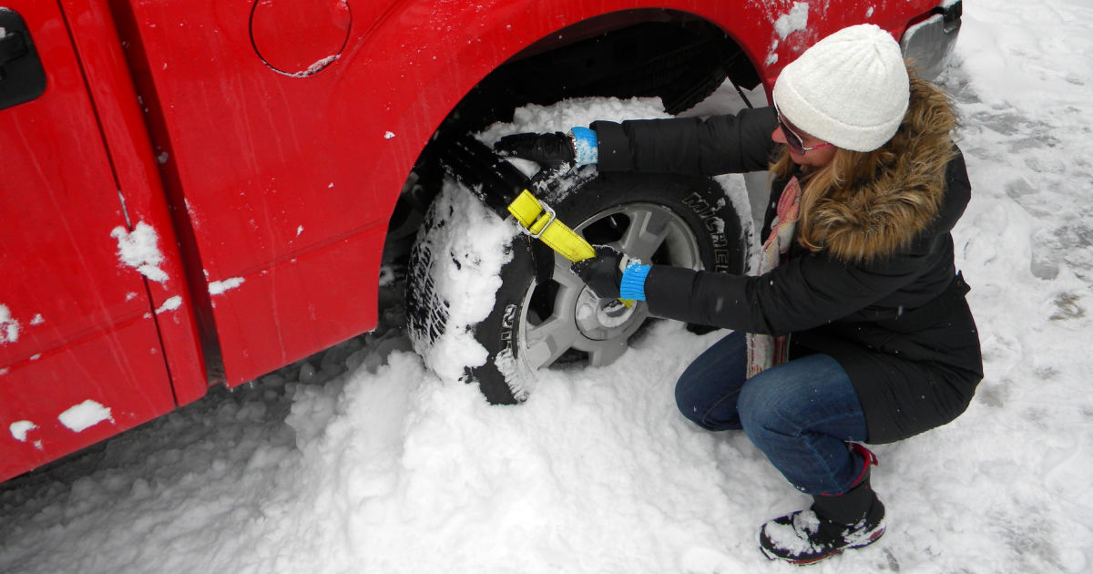 woman putting trac grabber on red truck