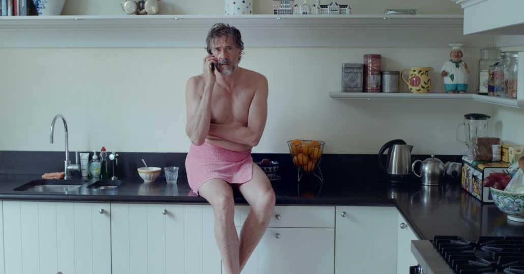 man sitting on kitchen counter wearing towel talking on phone.