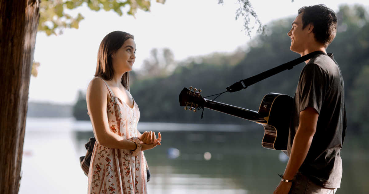 teen girl talking with teen boy with guitar by lake.
