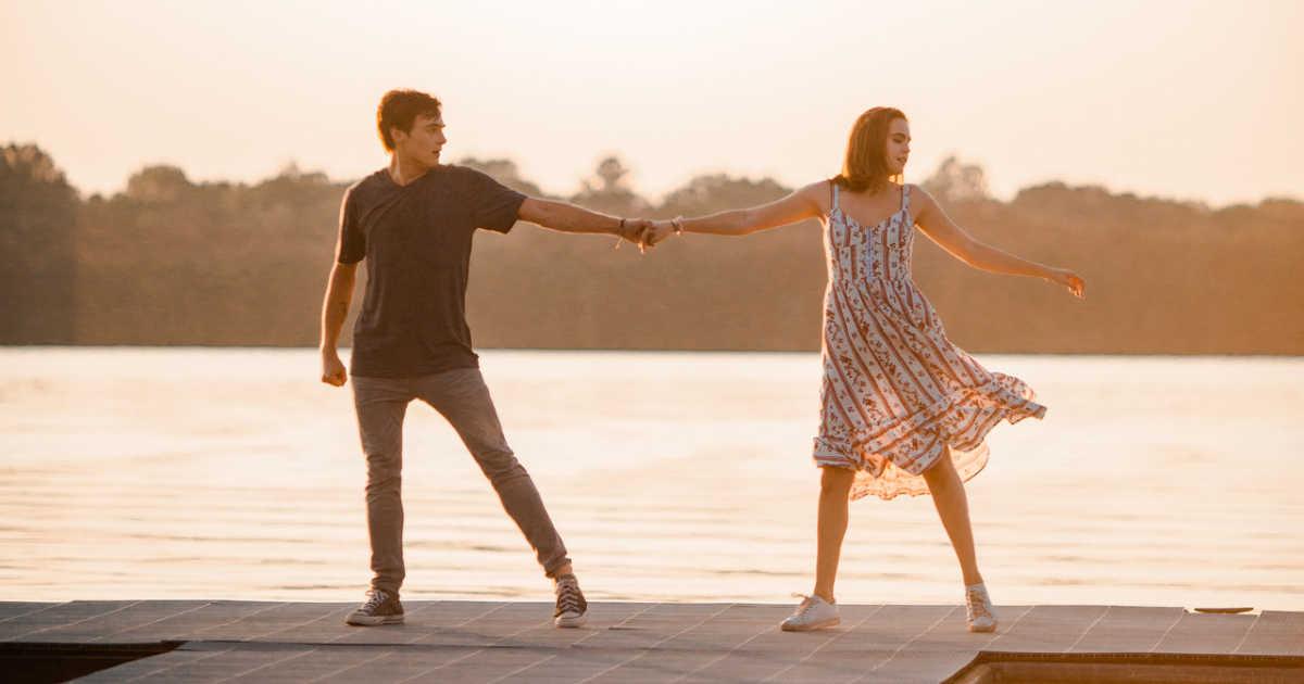 teens dancing on dock by lake.