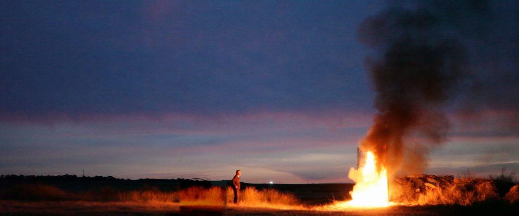 man watching fire burn