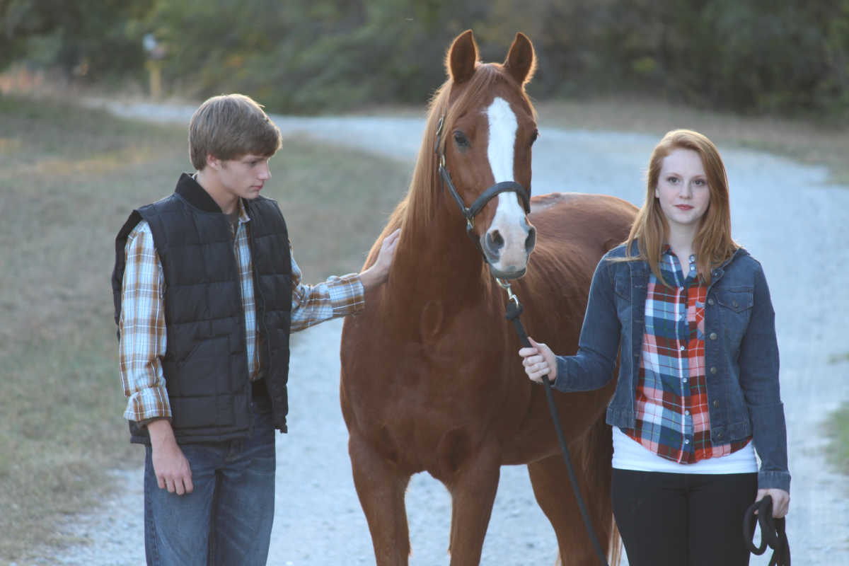 two teenagers with horse